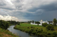 The river surrounds the old monastery. There`s a storm coming. Suzdal, Russia. Summer landscape, The river surrounds the old monastery. There`s a storm coming stock photos
