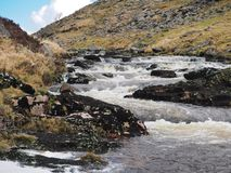 River Tavy cascading over rocks through the Tavy Cleave, Dartmoor National Park, Devon, UK. River Tavy water cascading over black lichen covered rocks through royalty free stock photos