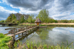 The River Test in Hampshire. A thatched fisherman`s hut and eel traps on the river Test at Longstock in Hampshire stock images