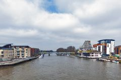 The River Thames flowing pass the city of Kingston upon Thames in Greater London, England. Kingston upon Thames, United Kingdom - April 2018: The River Thames Royalty Free Stock Images