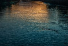 The  River Thames at sunset. The golden and blue light reflected in the Thames at sunset royalty free stock photography