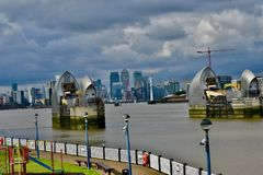 The river Thames and the thames barriers. The thames barriers across the thames river and the skyline of cannery wharf in London in the background royalty free stock photos