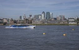 The river Thames - a view of the Canary Wharf; a tour boat. The image shows a view of the river Thames with the view of the Canary Wharf in the distance. It was royalty free stock photos