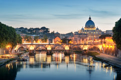River Tiber, Rome - Italy. Night image of River Tiber, Ponte Sant Angelo and St. Peter's Basilica in the background stock photo
