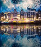 River, traditional old houses and boats, Amsterdam. Amstel river, canals and boats against night cityscape of Amsterdam with fireworks, Holland Netherlands stock photo