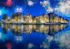 River, traditional old houses and boats, Amsterdam. Amstel river, canals and boats against night cityscape of Amsterdam with fireworks, Holland Netherlands royalty free stock image
