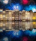 River, traditional old houses and boats, Amsterdam. Amstel river, canals and boats against night cityscape of Amsterdam with fireworks and reflection on water stock photos