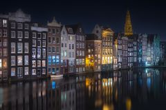 River, traditional old houses and boats, Amsterdam. Amstel river, canals and boats against night cityscape of Amsterdam, Holland Netherlands royalty free stock image