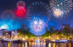 River, traditional old houses and boats, Amsterdam. Amstel river, canals and boats against night cityscape of Amsterdam with fireworks, Holland Netherlands royalty free stock photos