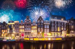 River, traditional old houses and boats, Amsterdam. Amstel river, canals and boats against night cityscape of Amsterdam with fireworks, Holland Netherlands royalty free stock photography