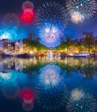 River, traditional old houses and boats, Amsterdam. Amstel river, canals and boats against night cityscape of Amsterdam with fireworks and reflection on water stock photo