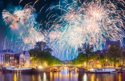 River, traditional old houses and boats, Amsterdam. Amstel river, canals and boats against night cityscape of Amsterdam with fireworks and reflection on water royalty free stock photography