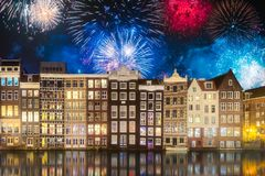 River, traditional old houses and boats, Amsterdam. Amstel river, canals and boats against night cityscape of Amsterdam with fireworks and reflection on water royalty free stock image