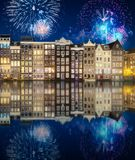 River, traditional old houses and boats, Amsterdam. Amstel river, canals and boats against night cityscape of Amsterdam with fireworks and reflection on water stock photography