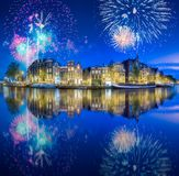 River, traditional old houses and boats, Amsterdam. Amstel river, canals and boats against night cityscape of Amsterdam with fireworks, Holland Netherlands stock images