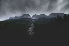River Between Trees and Mountains Under Grey Clouds during Daytime Royalty Free Stock Images
