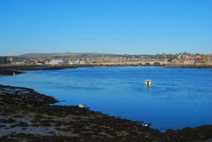 River Tweed estuary at Berwick-upon-Tweed  bridges and river. Looking up river Tweed to Berwick-upon-Tweed bridges,  houses, hills, boat and swan Royalty Free Stock Photography