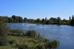 River between two banks on blue sky background royalty free stock images