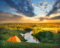 River under a hill with an orange tent at sunset stock images