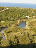 River valley by the sea. Panorama of Cedrino River canyon, river flowing to the sea at Cala Osalla, lush Mediterranean vegetation with pine trees and cactuses stock images