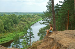 River view. Young woman sitting and meditate on steep with peaceful river view Royalty Free Stock Photo
