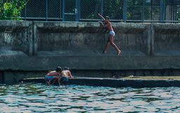 River view of little boys playing at the bay. Children jumping into the water. royalty free stock image