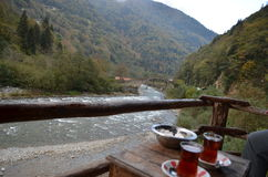 River view with tea, Turkey. Wood table with Turkish tea on patio next to rive in Black Sea region of Turkey Stock Images