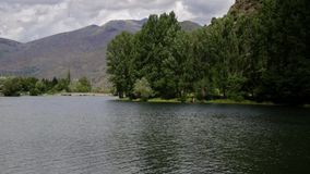 River view with trees and the water surface moved by the wind:Time Lapse. River view with trees and the water surface moved by the wind, mountains and cloudy sky stock footage