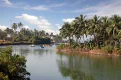 River with village on banks. A picture of a river in India, with a small village along its banks. Some small boats are floating along as well Royalty Free Stock Photo