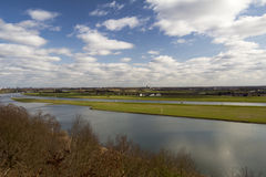River vista. The Dutch river Rhine is surpassed by soft clouds on a warm spring day. The water looks smooth Royalty Free Stock Images