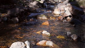 River Water Flow Between Rocks and Stones in Mountains Slider Pull. A pulling slider shot of a creek in the mountains. Water flows between stones stock video footage