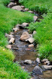 River Water on Rocks. River water flowing past rocks and stones in green meadow Stock Image