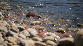 River waves beating against coastal rocks making them wet. stock video footage