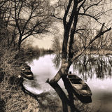 River With Trees And Boats In Sepia Look Stock Images