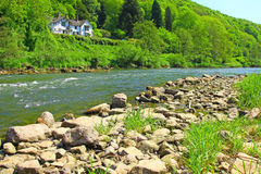 River Wye - Wye Valley  - England/Wales. The River Wye depicted with rocks in the foreground and a house located high up on the bank of the river Royalty Free Stock Image