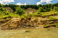 Riverbank auf dem Fluss, der Zeichen der Bankabnutzung zeigt Stockbild