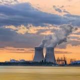 Riverbank con la central nuclear Doel durante una puesta del sol con las nubes dramáticas, puerto de Amberes imágenes de archivo libres de regalías