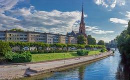 Riverbank e iglesia verdes en fondo del cielo azul en verano fotografía de archivo libre de regalías