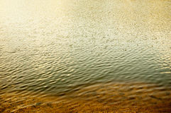 Riverbank, sand and rippled water with reflections a lot of copyspace Royalty Free Stock Photography