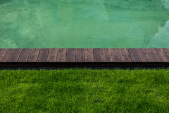 Riverbank with wooden path and green lawn Stock Image