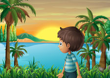 A riverbank with a young boy Royalty Free Stock Image