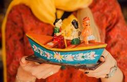 Riverboat met Indische familie in vormen van kleurrijk houten stuk speelgoed in in traditionele stijl van India, in handen van vr Stock Afbeeldingen