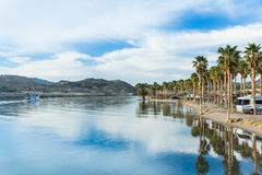 Tranquil Waters of the Colorado River. A riverboat tour passes an RV campground on the shore of the Colorado River in Laughlin, Nevada, with sunshine and palm Royalty Free Stock Photography