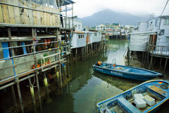 Riverboats of fishermen near metal houses on wooden stilts in poor village Stock Image