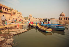Riverboats with relaxing people on river with ancient indian towers around in India. JAISALMER, INDIA - FEB 2: Riverboats with relaxing people on river with royalty free stock photography
