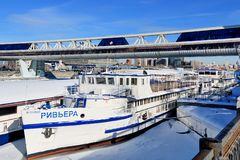 Moscow, Russia - February 14, 2019: River vessels moored to the bank of the Moscow-frozen river and the Bagration bridge royalty free stock photo