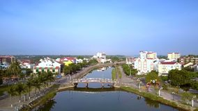 Riverfront with palms bridge and white buiding reflects on water. Beautiful Hoian riverfront with high palms and bridge over channel and white buiding reflects stock video footage