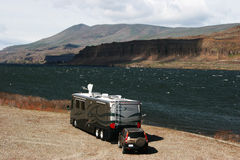 Riverfront RV Camping. An RV parked along the banks of a mighty river Royalty Free Stock Images
