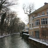Riverhouse. House on the snowy bank of a river royalty free stock photo