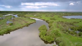 Rivers and lakes surrounded by green grass and trees. Exciting rivers and lakes surrounded by green grass and trees against small village under pictorial sky stock footage